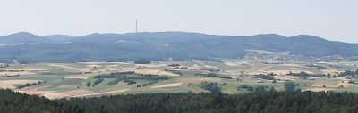 Blick vom 10-16km östlich gelegenen Christenberg im Burgwald auf Hassernroth (622m), Hainpracht (631m, Hintergrund), und den breiten Gipfel der 674m hohen Sackpfeife vom Wieschen (652m, links) über die Sendeanlage bis hin zum höchsten Punkt; schließlich die 583m und ca. 560m hohen Brüste des Kohlenberges - Ausschnitt eines Bildes aus Wikipedia.